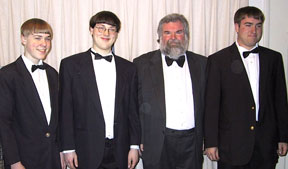 The four band members in formal black concert dress with bow ties